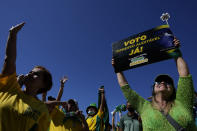 """A supporter of Brazil's President Jair Bolsonaro carries a sign that reads in Portuguese """"Printed and auditable vote,"""" during a pro-Bolsonaro rally at the Esplanade of Ministries, in Brasilia, Brazil, Sunday, Aug. 1, 2021. Political backers of President Bolsonaro have called for nationwide rallies to express their support for the embattled leader and his call for adding printouts to the electronic voting system. (AP Photo/Eraldo Peres)"""