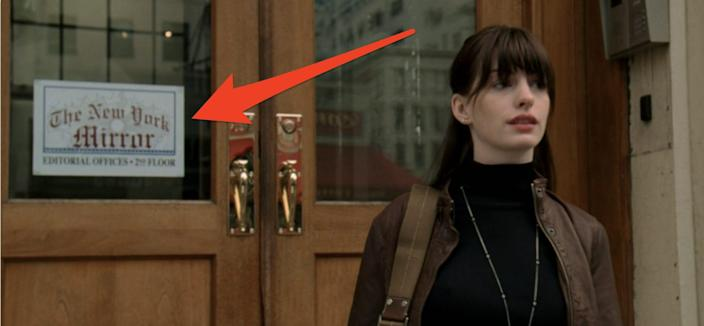 red arrow pointing to the new york mirror sign as andy walks out of the office devil wears prada