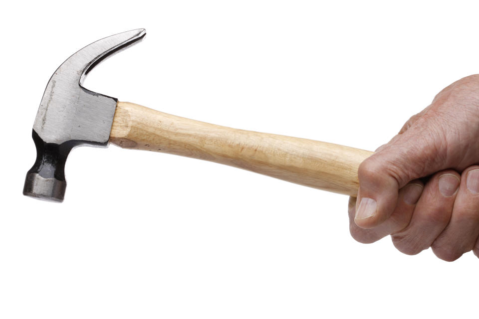 A man's hand holding a hammer. (PHOTO: Getty Images)