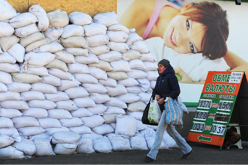 A woman walks near a shop and a pile of sandbags in the centre of Donetsk, eatern Ukraine, on October 26, 2014