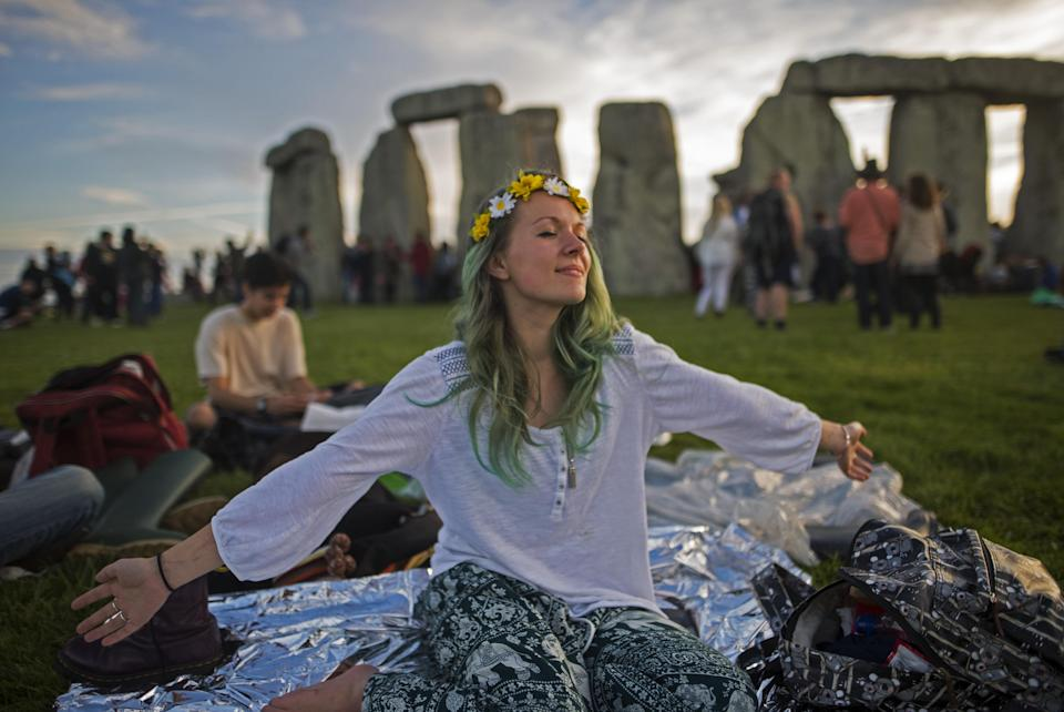 A woman celebrates the summer solstice at Stonehenge in 2017 (Rex)