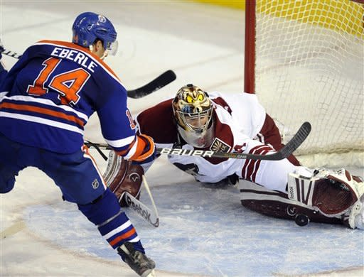 Edmonton Oilers' Jordan Eberle (14) scores on Phoenix Coyotes goaltender Mike Smith during the second period of an NHL hockey in Edmonton on Sunday, March 18, 2012. (AP Photo/The Canadian Press, John Ulan)