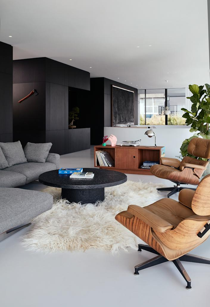 """<div class=""""caption""""> The living room features a vintage brutalist coffee table and two rare cream-colored Eames chairs, both sourced by vintage specialists Morentz. The carpet is handmade from the wool of biodynamic Dutch sheep. </div>"""