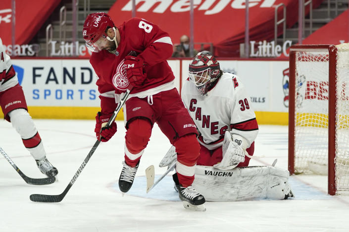 Detroit Red Wings center Sam Gagner (89) tries to redirect a shot on Carolina Hurricanes goaltender Alex Nedeljkovic (39) in the second period of an NHL hockey game Sunday, March 14, 2021, in Detroit. (AP Photo/Paul Sancya)