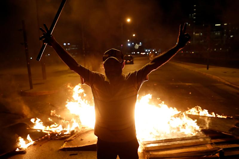 An anti-government protester flashes the victory sign as others burn wood to block a road during a protest against the political leadership they blame for the economic and financial crisis, in Beirut, Lebanon, Thursday, June 11, 2020. (AP Photo / Hussein Malla)