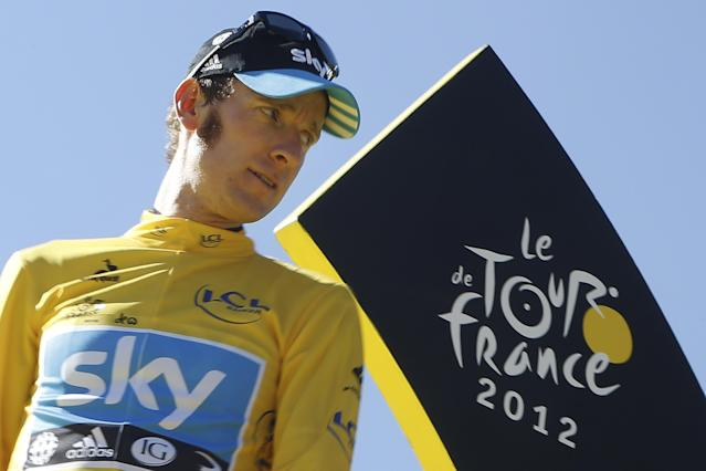 "FILE - In this Sunday, July 22, 2012 file photo, Bradley Wiggins, winner of the 2012 Tour de France cycling race, looks back on the podium in Paris, France. Former Tour de France champion Bradley Wiggins says he is ""gutted"" and likely to miss this year's race as his team is focusing on his bitter rival and defending champion Chris Froome's title defense. Wiggins told BBC Breakfast program on Friday, June 6, 2014, ""as it stands, I won't be there. The team is focused around Chris Froome. I am gutted. I've worked extremely hard for this throughout the winter and up to the summer. I feel I am in the form I was two years ago."" (AP Photo/Laurent Cipriani, File)"