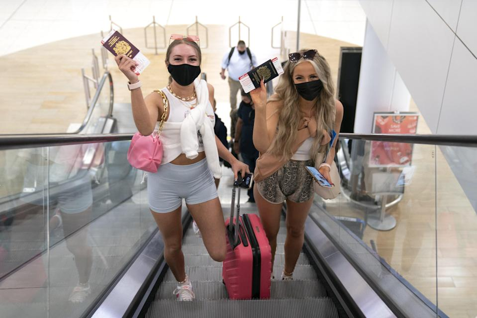 Twenty-year-old friends Poppy (left) and Shannon head for the departure gate (Jane Barlow/PA) (PA Wire)