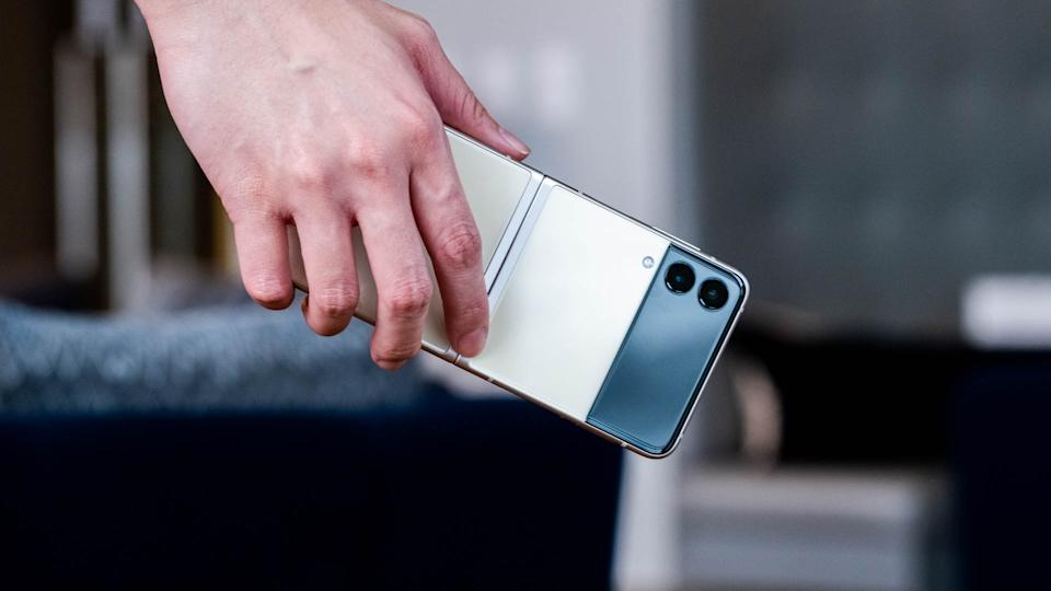 The Samsung Galaxy Z Flip 3 unfolded in someone's hand, with its rear facing the camera