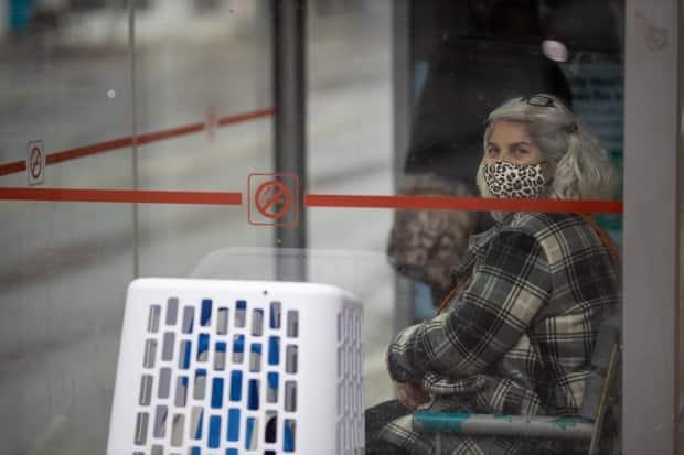 An OC Transpo passenger wearing a mask waits for her bus on April 29, 2021. (Andrew Lee/CBC - image credit)