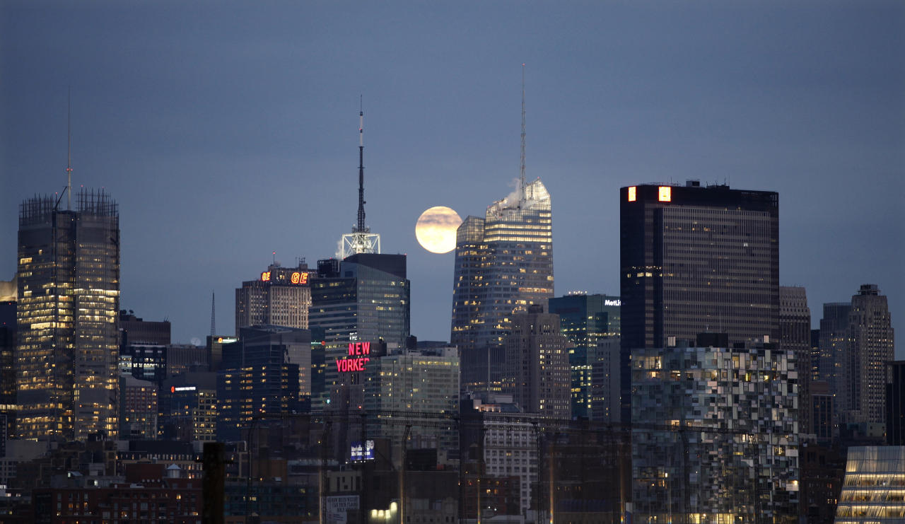 A full moon rises behind the skyline of midtown Manhattan in New York. (Gary Hershorn / Reuters)