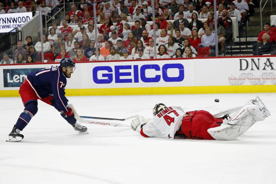 Carolina Hurricanes goaltender James Reimer (47) pokes the puck away from Columbus Blue Jackets' Nick Foligno (71) during the first period of an NHL hockey game in Raleigh, N.C., Saturday, Oct. 12, 2019. (AP Photo/Karl B DeBlaker)