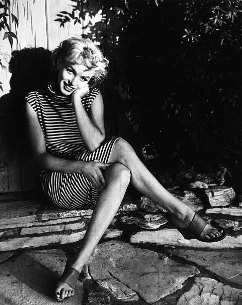 """<p>Raised mostly by foster parents because her own mother battled mental health issues, Marilyn rose from nothing to international stardom. Signing with Twentieth Century Fox in 1947, Monroe's career began to skyrocket in the early '50s with her roles in <a href=""""https://www.amazon.com/Niagara-Colorized-Marilyn-Monroe/dp/B002D40X2Q/?tag=syn-yahoo-20&ascsubtag=%5Bartid%7C10055.g.34743066%5Bsrc%7Cyahoo-us"""" rel=""""nofollow noopener"""" target=""""_blank"""" data-ylk=""""slk:Niagara"""" class=""""link rapid-noclick-resp"""">Niagara </a>(1953), <a href=""""https://www.amazon.com/Gentlemen-Prefer-Blondes-Jane-Russell/dp/B009EDZYZ0/?tag=syn-yahoo-20&ascsubtag=%5Bartid%7C10055.g.34743066%5Bsrc%7Cyahoo-us"""" rel=""""nofollow noopener"""" target=""""_blank"""" data-ylk=""""slk:Gentlemen Prefer Blondes"""" class=""""link rapid-noclick-resp""""><em>Gentlemen Prefer Blondes</em></a> (1953), <em>How to Marry a Millionaire</em> (1953), and <em>There's No Business Like Show Business</em> (1954). She soon became a household name and an international sex symbol.</p>"""