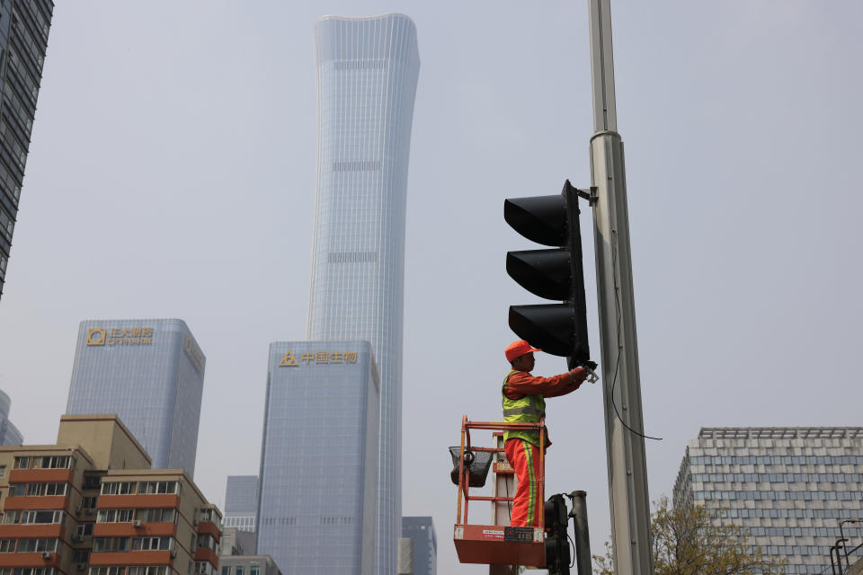 A worker installs new traffic lights at a junction in Beijing on Thursday, April 15, 2021. China's economic growth surged to 18.3% over a year earlier in the first quarter of this year as factory and consumer activity recovered from the coronavirus pandemic. (AP Photo/Ng Han Guan)