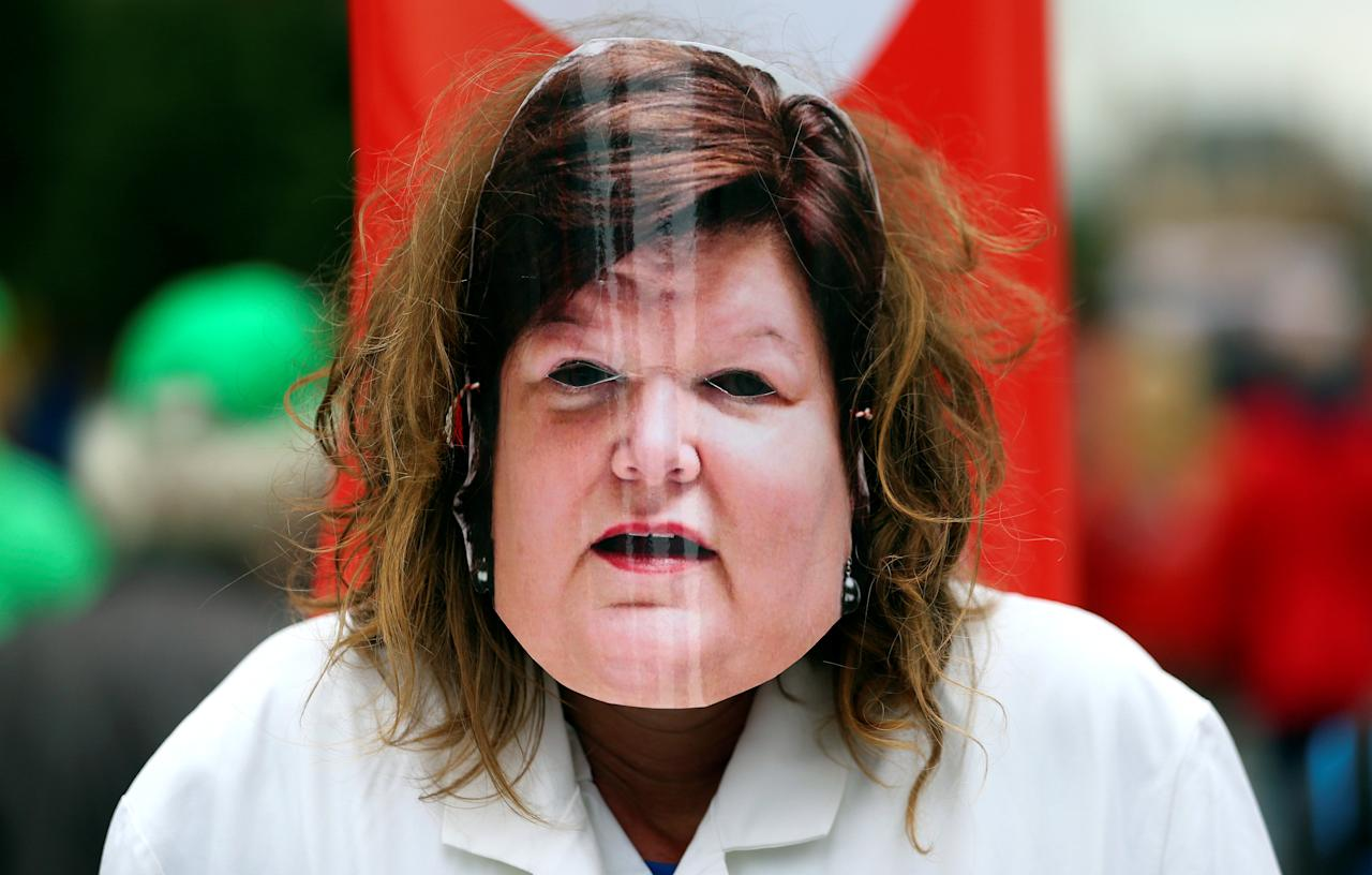 A woman wears a mask depicting Belgian Health Minister Maggie De Block during a protest over the government's reforms and cost-cutting measures, in Brussels, Belgium September 29, 2016. REUTERS/Yves Herman