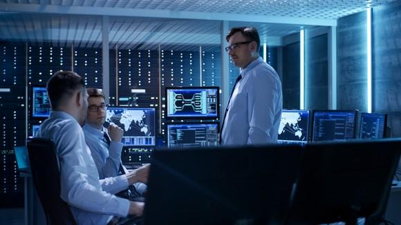 A group of tech workers conferring in a room full of computer screens and blinking LED lights