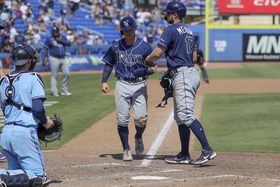 Tampa Bay Rays' Austin Meadows, right, celebrates as his walk scores Taylor Walls in front of Toronto Blue Jays catcher Danny Jansen during the ninth inning of a baseball game Sunday, May 23, 2021, in Dunedin, Fla. (AP Photo/Mike Carlson)