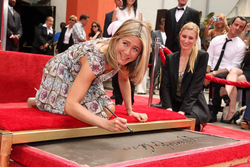 """After nearly 20 years in the biz, Jennifer Aniston was given a big celebrity honor -- a Hand and Footprint Ceremony at Grauman's Chinese Theatre in Hollywood on Thursday. And to top things off, her new beau, Justin Theroux, shaved his beard and cleaned up nicely to be by her side at the event. Eric Charbonohneau/<a href=""""http://www.wireimage.com"""" target=""""new"""">WireImage.com</a>- July 7, 2011"""