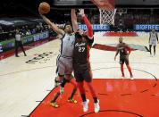 San Antonio Spurs forward Keldon Johnson, left, drives to the basket on Portland Trail Blazers center Jusuf Nurkic during the first half of an NBA basketball game in Portland, Ore., Saturday, May 8, 2021. (AP Photo/Steve Dykes)
