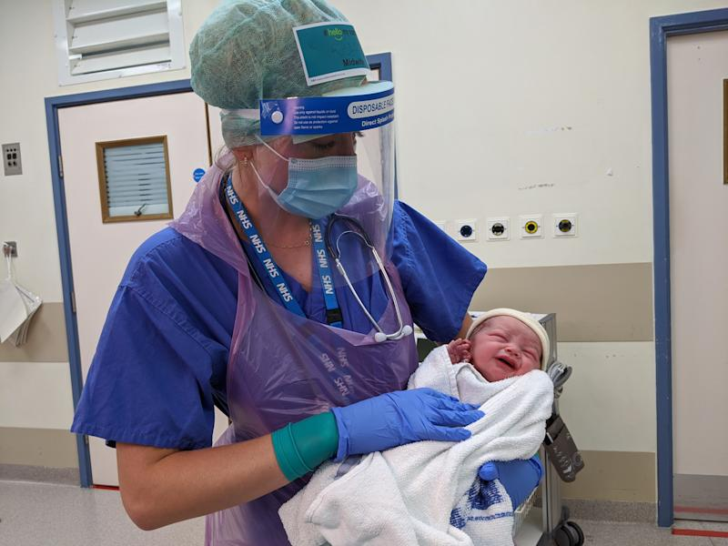One image shows a midwife in full PPE having delivered a baby. (Kensington Palace)