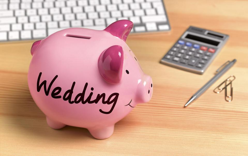 """A piggy bank with the word """"Wedding"""" written on the side next to a calculator and pen"""