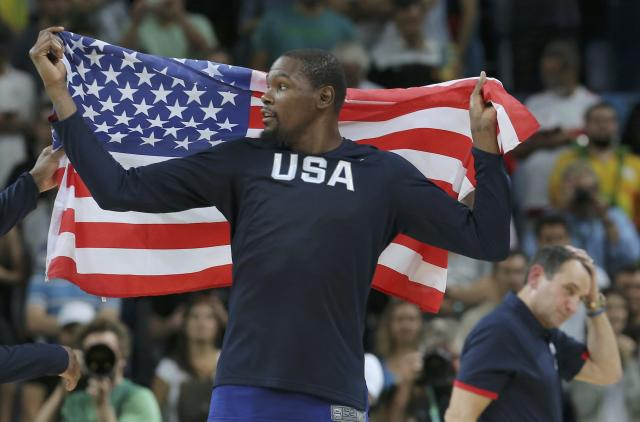 2016 Rio Olympics - Basketball - Final - Men's Victory Ceremony - Carioca Arena 1 - Rio de Janeiro, Brazil - 21/8/2016. Kevin Durant (USA) of the USA carries U.S flag as Head coach Mike Krzyzewski (USA) of the USA walks behind him. REUTERS/Jim Young FOR EDITORIAL USE ONLY. NOT FOR SALE FOR MARKETING OR ADVERTISING CAMPAIGNS.