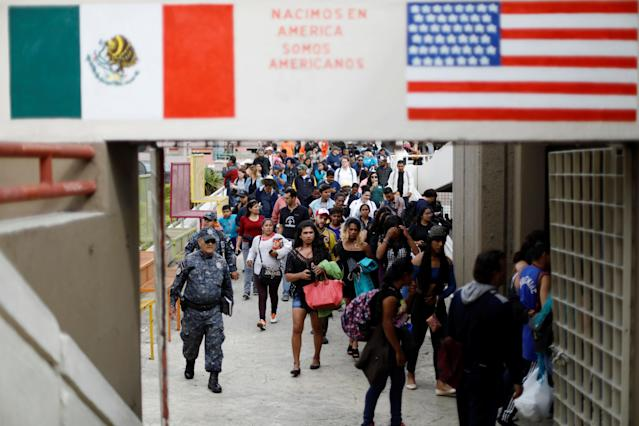 """<p>Members of a caravan of migrants from Central America walk towards the United States border and customs facility, where they are expected to apply for asylum, in Tijuana, Mexico April 29, 2018. The sign between the Mexican and the U.S. flag reads: """" We were born in America, we are Americans."""" (Photo: Edgard Garrido/Reuters) </p>"""