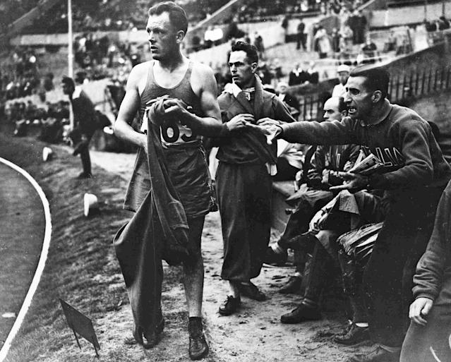 An Italian representative protests from the side of the track over the elimination of France's Louis Chevalier, left, from heat two of the men's 10,000-metres Olympic Games Walk at Wembley Stadium, London, Aug. 3, 1948, after officials had requested his retirement. Several competitors were removed for infringement of the rules of walking. (AP Photo)
