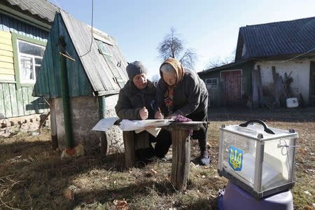 A local resident (R) fills in a ballot brought by an election commission member during a parliamentary election in Horodyshche near Chernihiv, October 26, 2014. REUTERS/Stringer