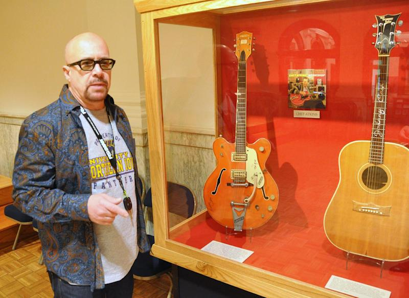This April 22, 2013 photo shows guitarist Robert Johnson, who played in the 1970s with Isaac Hayes and John Entwistle's Ox, talking about the Chet Atkins and Johnny Cash guitars he donated to the National Music Museum in Vermillion, S.D. Johnson also donated a guitar played by Elvis Presley during his final tour and a harmonic played by Bob Dylan. (AP Photo/Dirk Lammers)