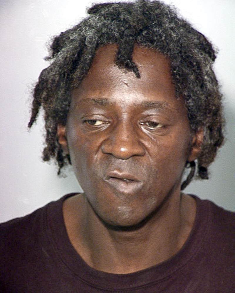 File - This Oct. 17, 2012 file image released by the Las Vegas Police Department shows rapper Flavor Flav, also known as William Jonathan Drayton, Jr., in a police booking photo. Entertainer FlavorFlav is expected to plead not guilty in Nevada state court to felony charges alleging he chased and threatened his longtime girlfriend's 17-year-old son with a butcher knife during a family argument last October. (AP Photo/Las Vegas Police Department, file)
