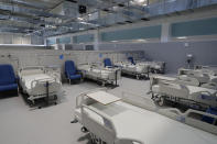New beds sit in the empty Isabel Zendal new hospital during the official opening in Madrid, Spain, Tuesday, Dec. 1, 2020. Authorities in Madrid are holding a ceremony to open part of a 1,000-bed hospital for emergencies that critics say is no more than a vanity project, a building with beds not ready to receive patients and unnecessary now that contagion and hospitalizations are waning. Spain has officially logged 1.6 million infections and over 45,000 deaths confirmed for COVID-19 since the beginning of the year. (AP Photo/Paul White)