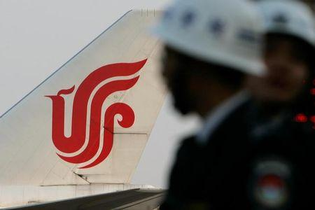 Security guards stand near an Air China aircraft on the tarmac of Shanghai Pudong International Airport