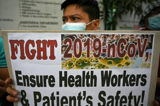 A health worker wearing a face mask holds a placard during a protest in front of a government hospital in Manila