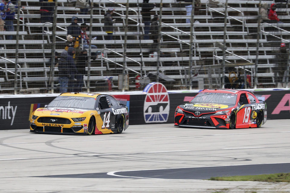 Clint Bowyer (14) and Martin Truex Jr. (19) make their way down the front stretch during the NASCAR Cup Series auto race at Texas Motor Speedway in Fort Worth, Texas, Wednesday, Oct. 28, 2020. (AP Photo/Richard W. Rodriguez)