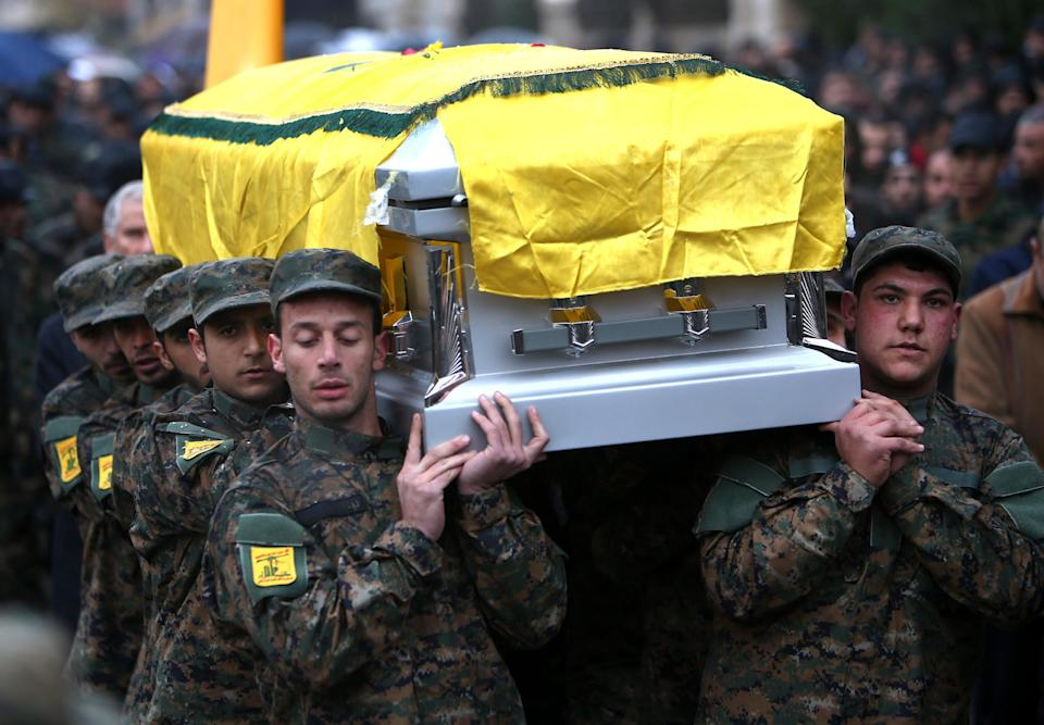In this December 4, 2013 photo, Hezbollah fighters carry the coffin of Hassan al-Laqis, a senior commander for the Lebanese militant group Hezbollah who was gunned down outside his home, during his funeral procession, at his hometown in Baalbek city, east Lebanon. The Shiite group has sent hundreds of its fighters into Syria to shore up President Bashar Assad's overstretched troops, helping them gain ground around the capital, Damascus, and near the Lebanese border. But with its own casualties mounting in a civil war that activists say has killed more than 150,000 people in three years, officials say Hezbollah has turned to a variety of new tactics - including complicated commando operations - to hunt down rebels and opposition commanders. (AP Photo/Hussein Malla)