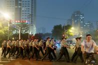 Officers of the People's Armed Police move into position as crowd control before a rehearsal of a fireworks display near the National Stadium ahead of the 100th founding anniversary of the Communist Party of China in Beijing