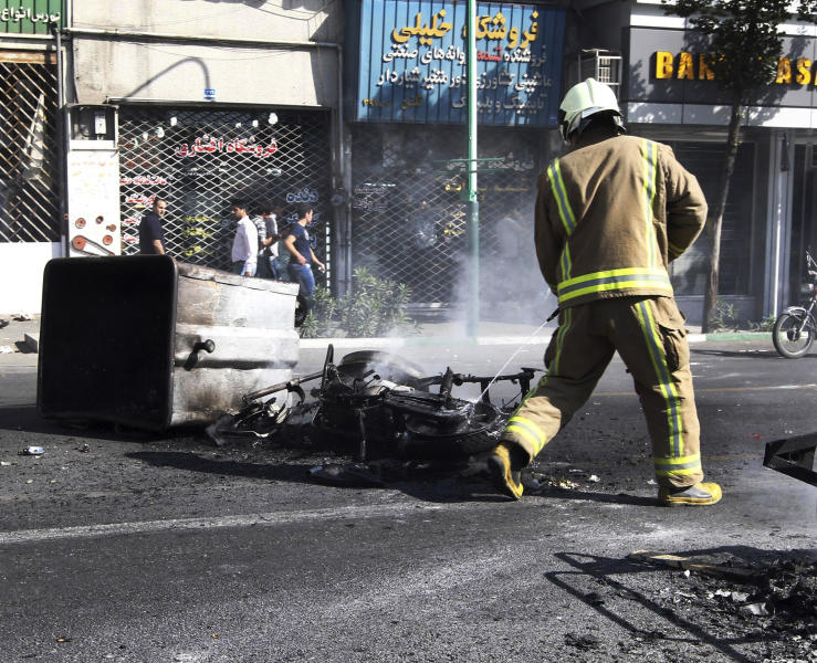 In this photo taken by an individual not employed by the Associated Press and obtained by the AP outside Iran, an Iranian fire fighter extinguishes a burned motorcycle in a street in central Tehran, near Tehran's old main bazaar, on Wednesday, Oct. 3, 2012. Police threatened merchants who closed their shops in Tehran's main bazaar and launched crackdowns on sidewalk money changers on Wednesday as part of a push to halt the plunge of Iran's currency, which has shed more than a third its value in less than a week. (AP Photo) EDITORS NOTE AS A RESULT OF AN OFFICIAL IRANIAN GOVERNMENT BAN ON FOREIGN MEDIA COVERING SOME EVENTS IN IRAN, THE AP WAS PREVENTED FROM INDEPENDENT ACCESS TO THIS EVENT.
