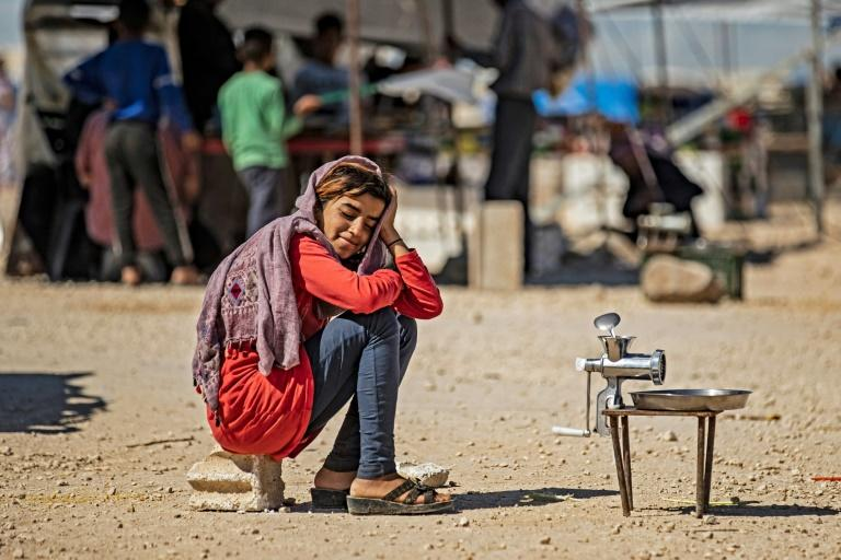 A Syrian girl waits for customers bringing chickpeas to grind for a fee at a camp for the internally displaced in Hasakeh province on May 10, 2020