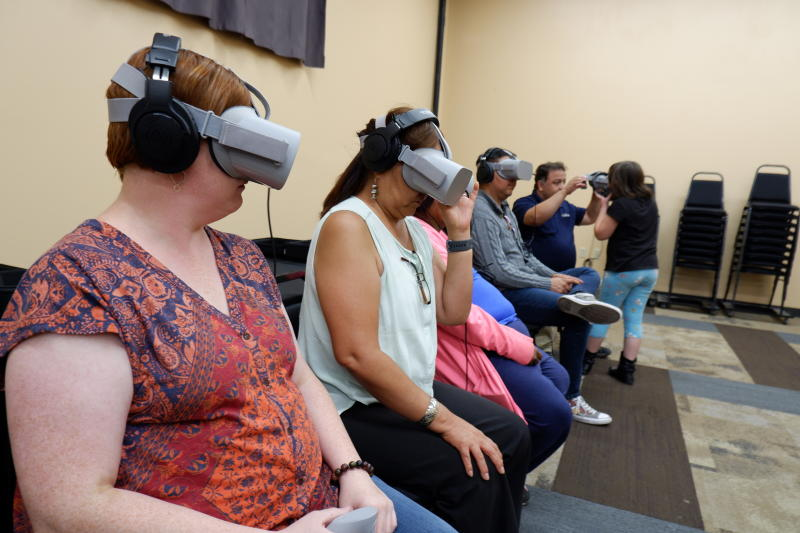 """In this Sept. 6, 2019, photo provided by Ways of Knowing, audience members try out virtual reality headsets to watch """"Ways of Knowing"""" a film titled """"Ways of Knowing,"""" which was directed by artist Kayla Briet, at the El Morro Events Center in Gallup, N.M. Briet and other activists were using virtual reality technology like a 360 VR video rig cameras to focus on areas of the Navajo Nation affected by uranium contamination. (Adriel Luis/Ways of Knowing via AP)"""