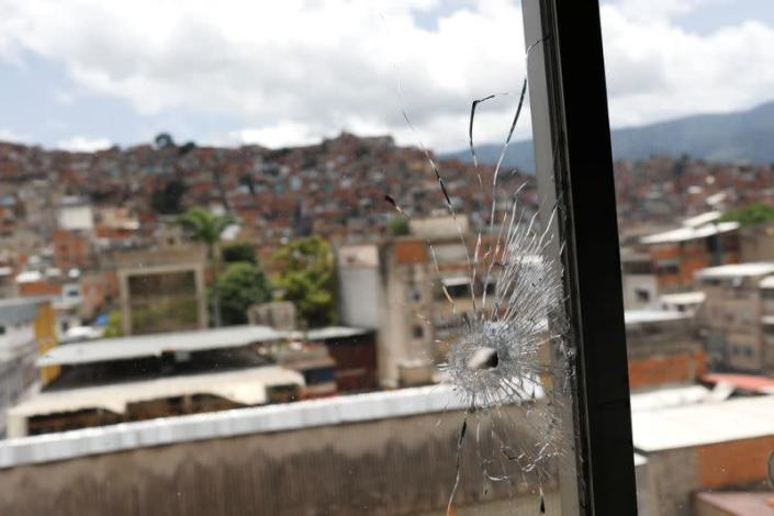 A window hit by a bullet is seen in the offices of the San Miguel Archangel church after armed confrontations between members of El Koki's criminal gang and police forces in the El Cementerio neighborhood, in Caracas