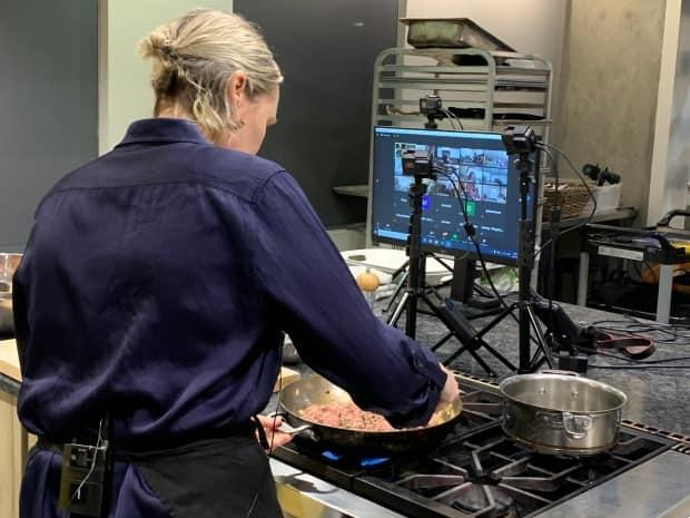 Kathryn Joel, cooks lamb in a skillet in her Get Cooking studio as class of students watch through a video chat and cook along in their kitchens at home.