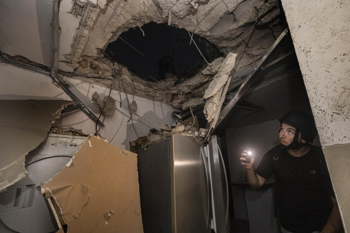 An Israeli man inspects the damage to a house that was hit by a rocket fired from the Gaza Strip, in Ashkelon, southern Israel, Wednesday, May 12, 2021. (AP Photo/Tsafrir Abayov)