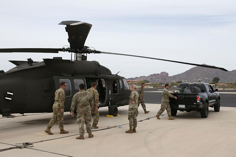 Members of an Arizona National Guard unit pause while loading a helicopter with medical supplies to be taken to the remote Navajo Nation town of Kayenta on March 31. (Photo: (AP Photo/Ross D. Franklin))