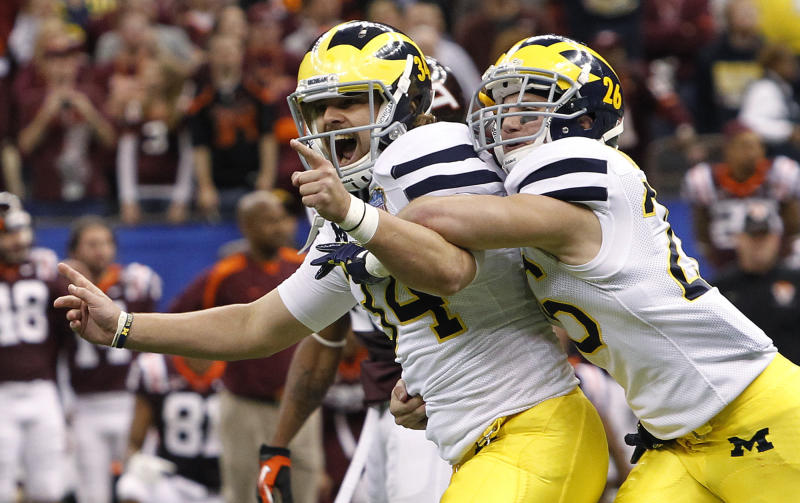 Michigan's Brendan Gibbons (34) is congratulated by Drew Dileo (26) after Gibbons kicked the winning field goal in overtime against Virginia Tech in the Sugar Bowl NCAA college football game in New Orleans, Tuesday, Jan. 3, 2012.  Michigan won 23-20. (AP Photo/Dave Martin)