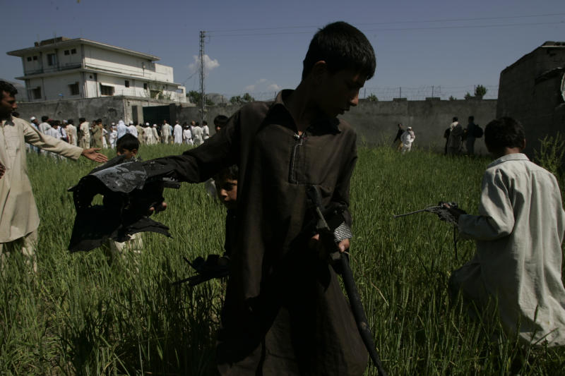 In this picture taken on May 3, 2011, a Pakistani youngster holds a metal pieces collecting them from wheat field outside a house, seen background, where it is believed al-Qaida leader Osama bin Laden lived in Abbottabad, Pakistan. Residents of this sleepy hill town in northwest Pakistan named after a British colonial officer are still trying to come to grips with their newfound infamy as home to one of the greatest mass murderers in modern history. (AP Photo/Anjum Naveed)