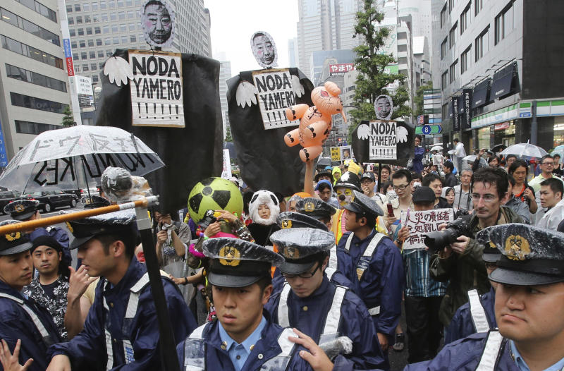 "Protesters carry effigies of Japanese Prime Minister Yoshihiko Noda as police officers accompany them during a march, protesting the restart of Ohi nuclear power plant, in Tokyo, Sunday, July 1, 2012. Noda ordered the restarts of the plant's two reactors last month, saying people's living standards can't be maintained without nuclear energy. Protesters were against a return to nuclear power because of safety fears after the Fukushima accident. The effigies read: ""Resign, Noda!"" (AP Photo/Shizuo Kambayashi)"