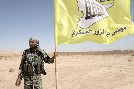 FILE PHOTO: A fighter from Deir al-Zor military council which fights under the Syrian Democratic Forces (SDF) holds the council's flag in the village of Abu Fas