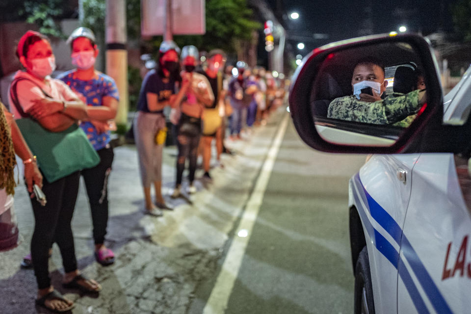 A police officer is reflected in the wing mirror as he reminds people queuing for a COVID-19 vaccine to observe social distancing, outside a vaccination site on August 08, 2021 in Las Pinas, Metro Manila, Philippines. (Photo:Ezra Acayan/Getty Images)