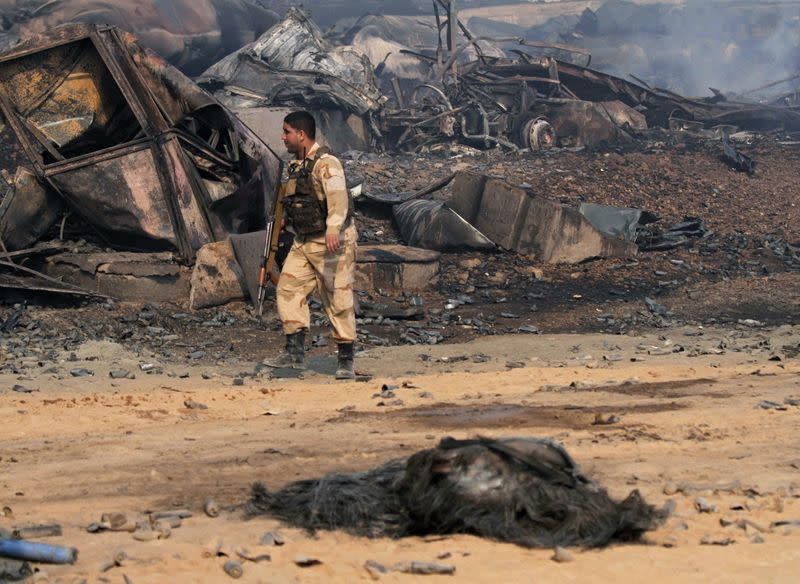An Afghan security officer walks past burnt tankers in Islam Qala