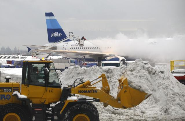A worker de-ices an airplane sitting at a gate near terminal C at LaGuardia Airport in the Queens borough of New York